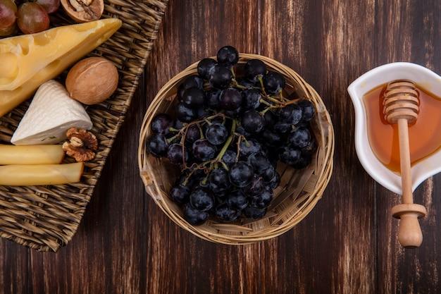 Vista dall'alto miele in un piattino con uve varietà di formaggi e noci su un supporto su uno sfondo di legno
