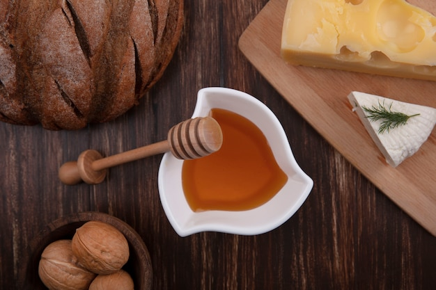 Top view honey in a saucer with a variety of cheeses on a stand with walnuts and a loaf of bread on a wooden background