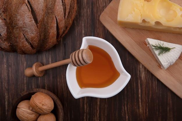 Vista dall'alto miele in un piattino con una varietà di formaggi su un supporto con noci e una pagnotta di pane su uno sfondo di legno