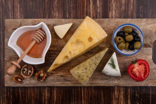 木製の背景の上のスタンドにチーズオリーブとトマトの品種と蜂蜜の上面図