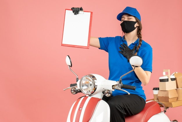 Vista dall'alto della speranzosa ragazza del corriere che indossa maschera medica e guanti seduta su uno scooter con in mano un foglio di carta vuoto che consegna ordini su sfondo color pesca pastello