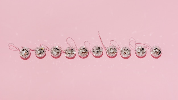 Top view horizontal line of christmas balls on pink background