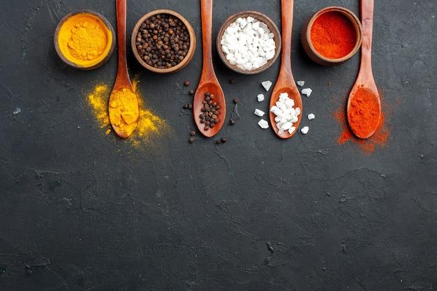 Vista dall'alto di ciotole di fila orizzontale con curcuma pepe nero sae sale pepe rosso in polvere cucchiai di legno sullo spazio libero tavolo nero