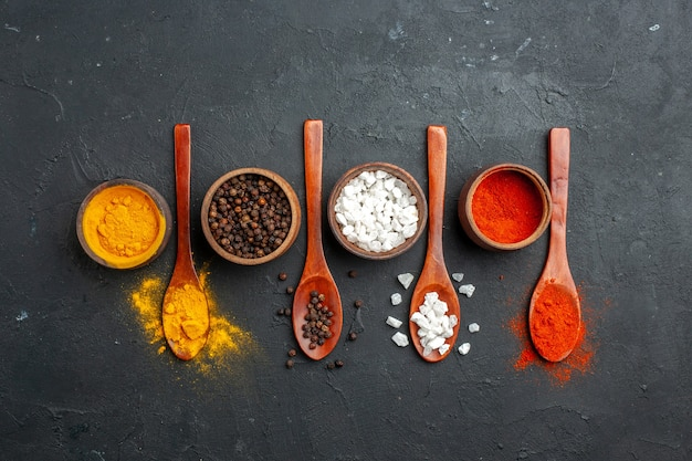 Top view horizontal row bowls with turmeric black pepper sae salt red pepper powder wooden spoons on black table