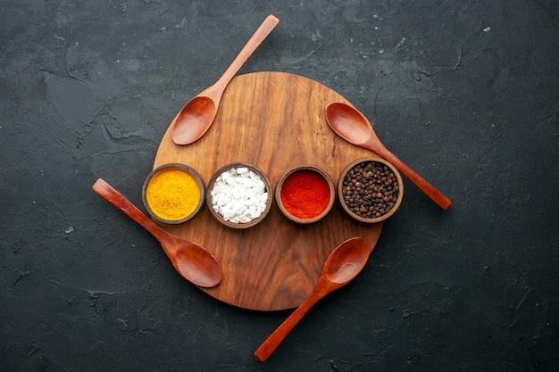 Вид сверху горизонтальные рядные миски с куркумой, красным перцем, морской солью с черным перцем, четыре ложки на круглой доске на темном столе с копией пространства