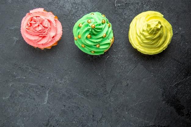 暗い表面の上面図水平列ミニカラフルなカップケーキ