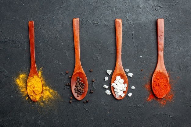 Top view horizontal row wooden spoons with turmeric black pepper sae salt red pepper powder on black table
