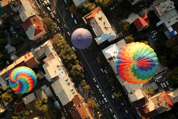 Top view of the hot air balloons over the old buildings of a city