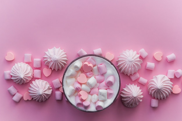 Top view hot beverage with whipped cream,marshmallows and heart shaped chocolate candies
