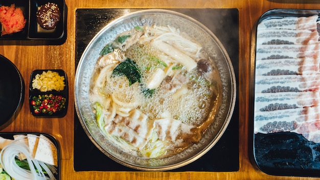 Top view of hot and boiling shabu broth with cabbage, eryngii, enotitake, tofu and kurobuta pork