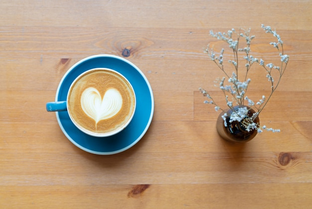 Top view of hot coffee cup and flower with a barista art heart foam on wooden table.