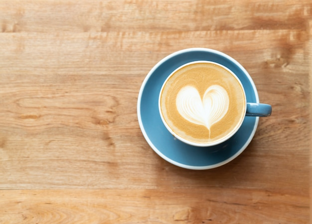 Top view of hot coffee cup with a barista art heart shape foam on wooden table background.