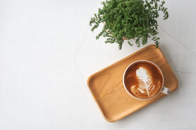 Top view of hot coffee latte cup with leaf shaped latte art milk foam on wooden tray and green small potted plant on white cracked concrete table background.