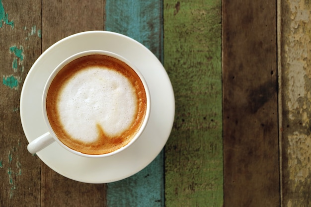 Top view of hot coffee with heart shaped milk foam served on rustic style wooden table