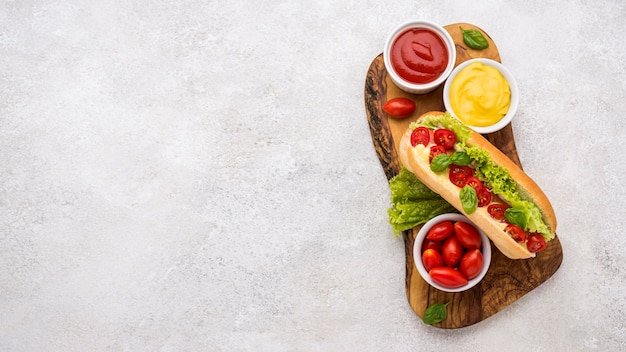 Вид сверху хот-дог с салатом и помидорами