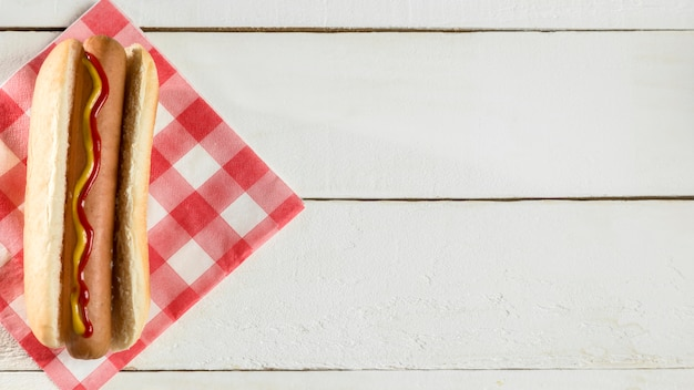Вид сверху хот-дог с салфеткой на деревянном фоне