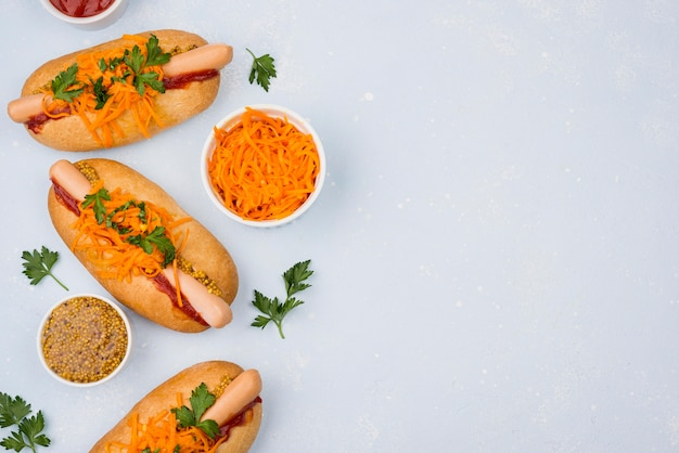 Top view hot dogs and carrots with copy-space