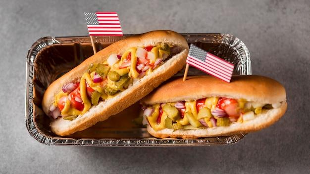 Vista dall'alto di hot dog con bandiera americana nel vassoio