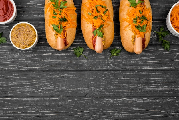 Top view hot dogs on wooden background