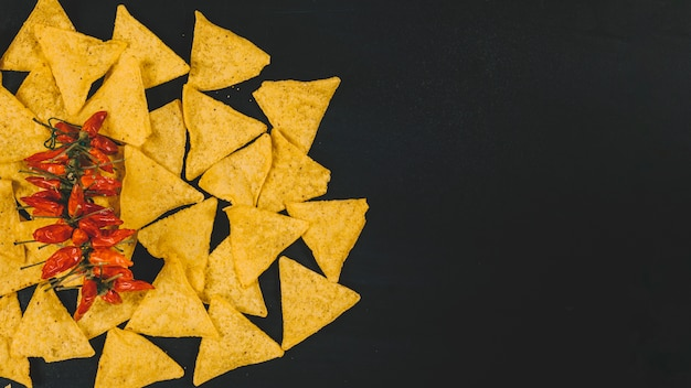 Top view of hot mexican nachos chips with red chilies over black backdrop