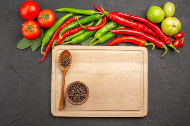 Top view hot red and green peppers and tomatoes bay leaves bowl of black pepper and spoon on a chopping board on black ground with free space