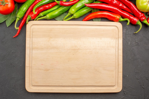 Vista dall'alto peperoni rossi e verdi caldi e foglie di alloro pomodori e un tagliere su fondo nero