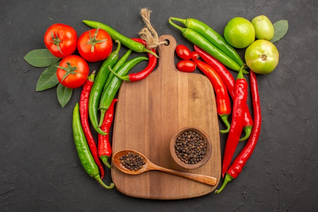 Top view hot red and green peppers tomatoes bowl of black pepper and spoon on a chopping board on black ground with free space