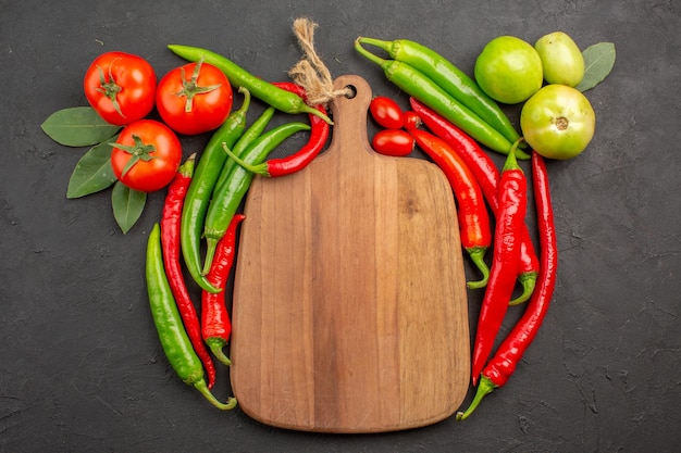 Top view hot red and green peppers tomatoes a chopping board on black ground with free space