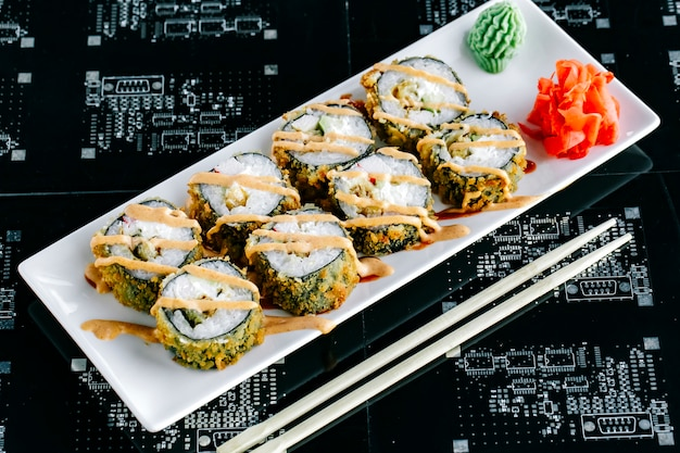 Top view of hot sushi rolls with avocado and crab stick garnished with spicy mayonnaise