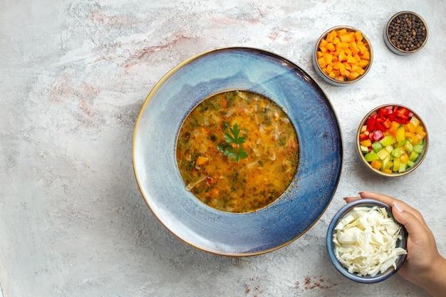 Zuppa di verdure calda vista dall'alto all'interno del piatto su uno spazio bianco-chiaro