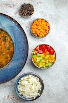 白いスペースのプレート内の上面図の熱い野菜スープ