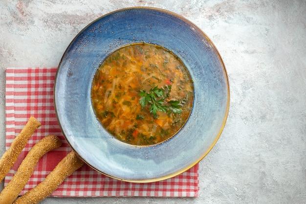 Zuppa di verdure calda vista dall'alto con verdure all'interno del piatto su uno spazio bianco
