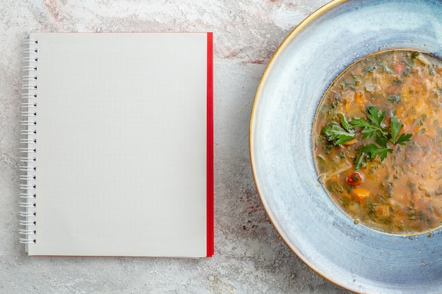 Top view hot vegetable soup with notepad on white space