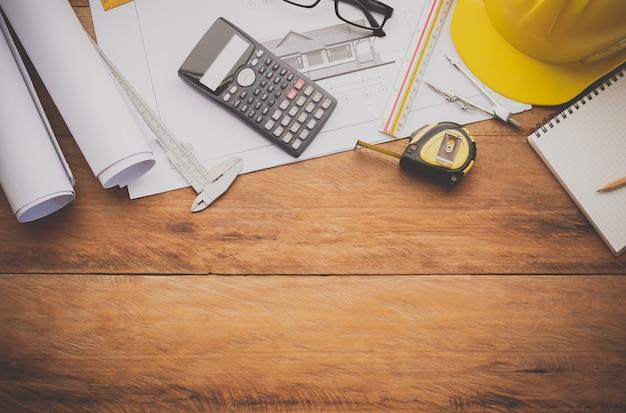 木の床に置かれた電卓、コンパス、コンパス、ヘルメットからなる家の青写真と作業機器。働くエンジニアのコンセプト機器