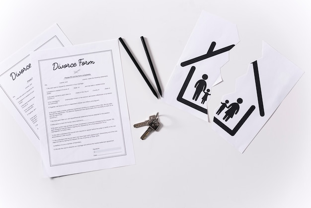 Top view house keys with divorce forms on the table