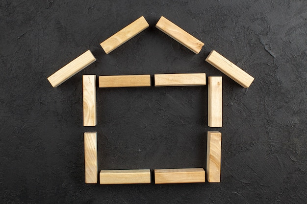 Blocchi di legno a forma di casa vista dall'alto sullo spazio della copia del tavolo nero