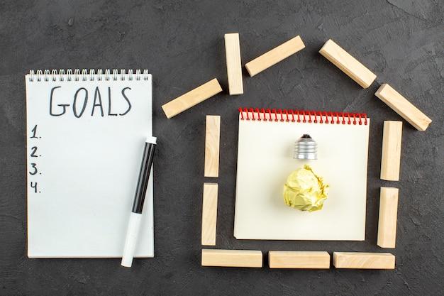 Obiettivi di blocchi di legno a forma di casa vista dall'alto scritti sul pennarello nero del blocco note su nero