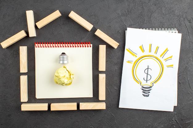 Vista dall'alto blocchi di legno a forma di casa obiettivi scritti sul blocco note idea lampadina che disegna sul blocco note su nero