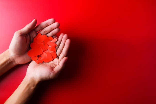 Top view human hand holding heart shaped paper on red background