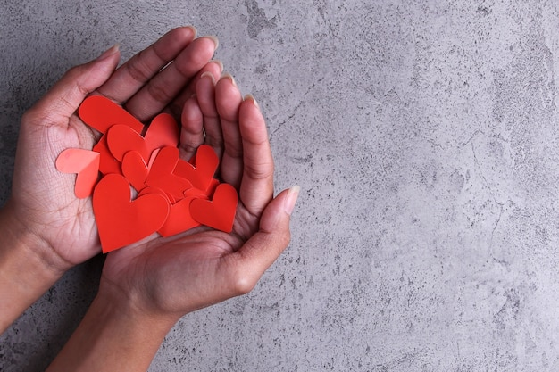 Top view human hand holding heart shaped paper on wall texture background