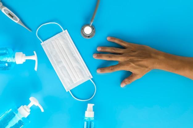 Вид сверху человеческая рука, цифровой термометр гигиенических масок, стетоскоп, спиртовой баллончик на синем столе. коронавирус предотвращение