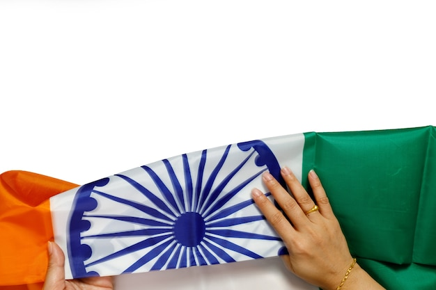 Top view of human hands holding a national flag of india on white background.