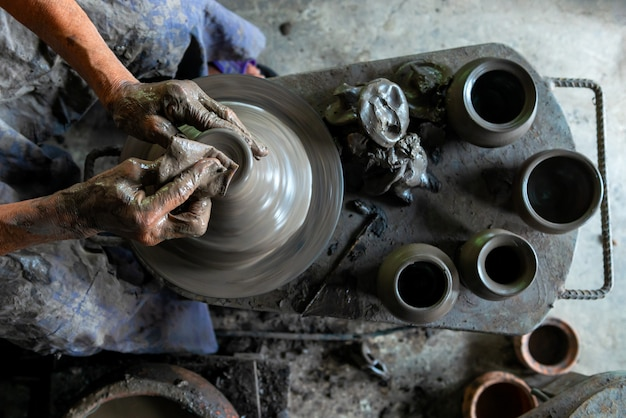 Top view of human hands working on pottery wheel at the workshop