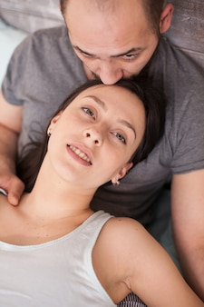 Top view of husband kissing his wife forehead after waking up in the morning.