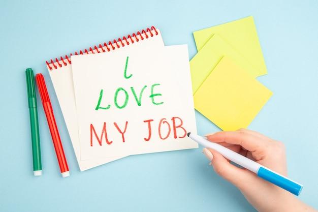 상위 뷰는 파란색에 여성 손 노란색 스티커 용지 마커에 스티커 메모 펜에 쓰여진 내 직업을 좋아합니다