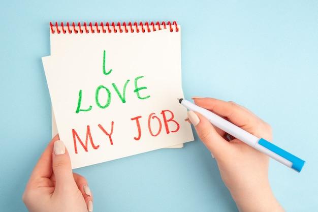 상위 뷰 나는 파란색에 여성 손에 스티커 메모 펜에 쓰여진 내 직업을 좋아합니다