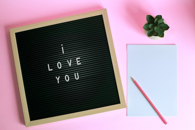 Top view of i love you on letter board with succulent and pencil on blank paper isolated on pink background