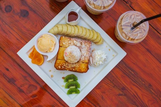 上面図新しい木製のテーブルの上のアイスクリームとコーヒーアイスティーフルーツ