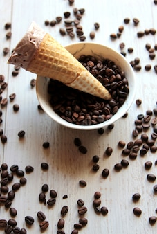 Top view of ice cream cone in a bowl filled with coffee beans on white