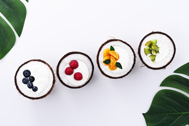 フルーツフィラー、白い背景の上のココナッツボウルのヨーグルト、トレンディなデザートの概念とトップビューアイスクリーム